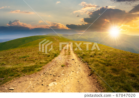 mountain road through grassy meadow at sunset. 67847020