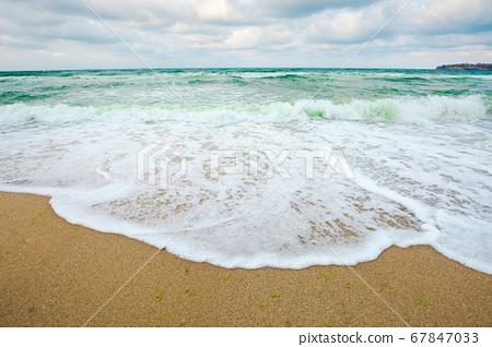 green sea waves beneath a grey sky. tide rolling 67847033