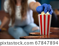 Woman wearing safety mask and gloves for Covid-19, coronavirus and quarantine watching television at home with red and white striped cupboard bucket with popcorn. Cinema and health concept 67847894
