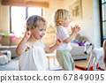 Portrait of small boy and girl playing indoors at home. 67849095