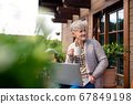 Senior woman with laptop and coffee sitting on terrace in summer, resting. 67849198