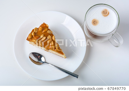 Latte coffee with a piece of cheesecake  67849770