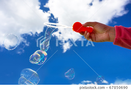 Young girl blowing soap bubbles into the sky 67850690