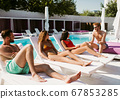 Group of young people having rest near the swimming pool 67853285