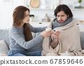 Attentive woman giving her sick boyfriend treatment 67859646