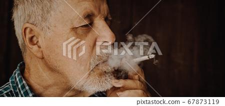 Senior man smoking cigarette outside, the cigarette addiction, unhealthy concept, bad habit 67873119