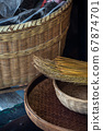 Vertical shot of woven baskets and a broom 67874701