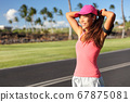 Active Asian runner woman tying hair into ponytail getting ready to run her morning jogging workout. Happy healthy lifestyle. Fitness wellness life 67875081