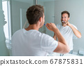 Man getting ready in the morning doing hygiene routine brushing his teeth looking in mirror of home bathroom using toothbrush in for clean dental oral care 67875831