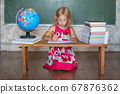 Little girl teaches home lessons on a bench against the background of the globe and books. 67876362