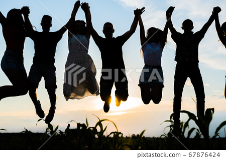Silhouettes of jumping friends on a sunset background. 67876424