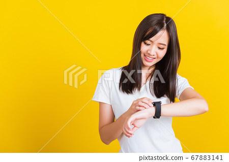 Young woman smiling looking and pointing finger 67883141