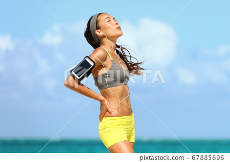 Tired woman runner exhausted breathing 67885696
