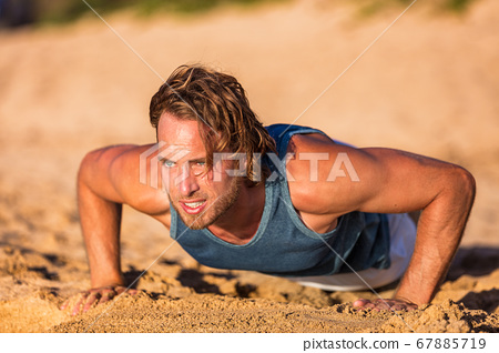 Push-up fitness man training pushups on beach doing bodyweight exercises for arms workout. Healthy lifestyle person working out muscles 67885719