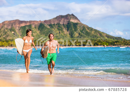 Happy surf people having fun surfing on Waikiki beach, Honolulu, Oahu, Hawaii. Asian woman, caucasian man multiracial couple running out of ocean splashing water. Summer vacations travel landscape 67885728