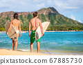 Hawaii surfers people relaxing on waikiki beach with surfboards looking at waves in Honolulu, Hawaii. Healthy active lifestyle fitness couple at sunset with diamond head mountain in the background 67885730