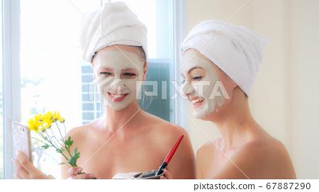Beautiful woman having a facial treatment at spa. 67887290