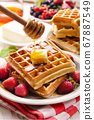 Belgian waffles served with butter strawberries 67887549
