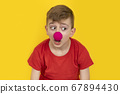 Child with clown nose on yellow background. 67894430