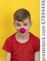 Teenager in red t-shirt with clown nose on yellow 67894446