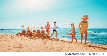 Happy kids on vacations at seaside running in the water 67895584