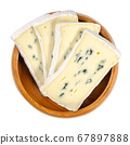Slices of soft cheese with white and blue mold in wooden bowl. Creamy cheese made of cow milk, surface ripened with white fungus and inside of the cheese a blue fungus. Closeup from above, food photo. 67897888