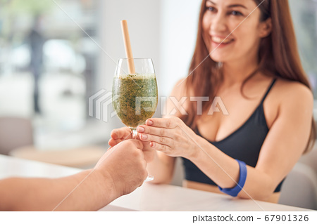 Female client rejoicing at her green smoothie 67901326