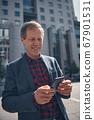 Handsome joyful man using smartphone on the street 67901531