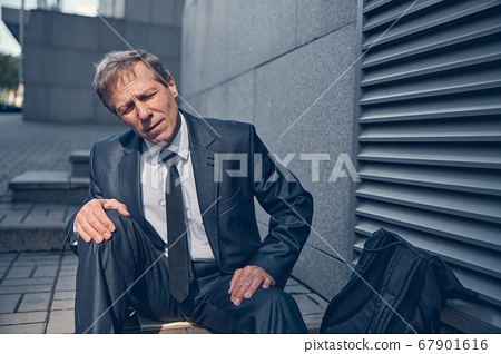 Tired unhappy man sitting on steps outdoors 67901616