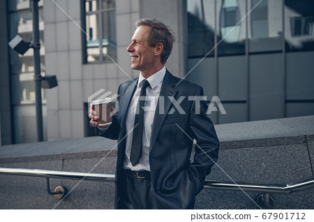 Joyful businessman drinking coffee on the street 67901712