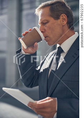 Handsome man drinking coffee and using tablet computer outdoors 67902235