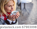 Smiling happy female spending time in the outdoors with coffee 67903098