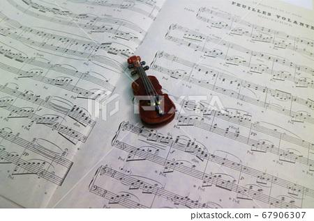 Miniature violin figurine on the score 67906307