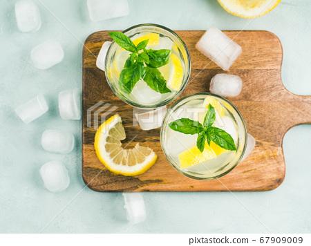 Fresh lemon lemonade in jug and glasses 67909009