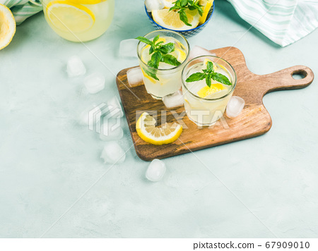 Fresh lemon lemonade in jug and glasses 67909010