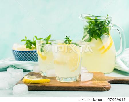 Fresh lemon lemonade in jug and glasses 67909011