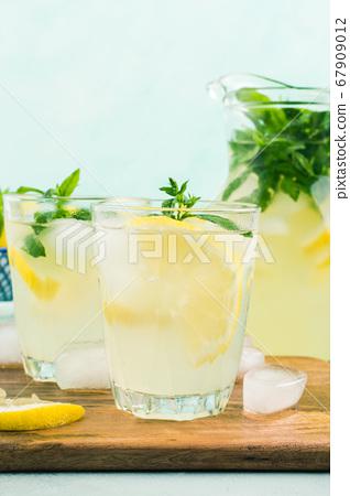 Fresh lemon lemonade in jug and glasses 67909012