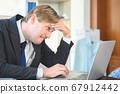 Stressful business man working and laptop on desk 67912442