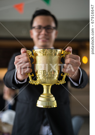 Asian businessman holding a golden trophy cup to cheerful and celebrated his successful in career and mission. concept of winner and competition. 67916647