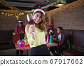 Asian woman holding a glass of champagne at the party. concept of party, drinks, holidays, and celebration. 67917662
