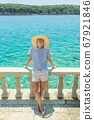 Rear view of woman wearing straw summer hat ,leaning against elegant old stone fence of coastal villa, relaxing while looking at blue Adriatic sea, on Losinj island Croatia. 67921846