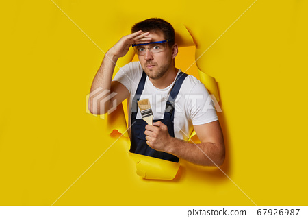 worker in safety glasses and uniform holding paint brush 67926987