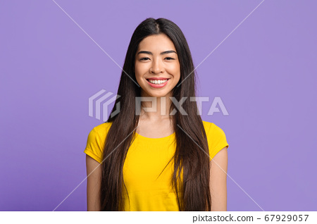 Portrait of smiling asian girl with beautiful long hair on purple background 67929057