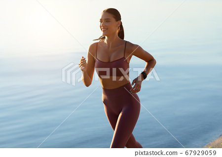Girl in sports bra and leggins running on the beach 67929059