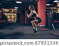 Beautiful young sporty woman training, workout in gym 67931336