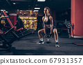 Beautiful young sporty woman training, workout in gym 67931357