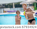 Wet and funny dad with son with water gun 67934924