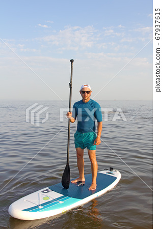 SAP Board surfing. Man is training on a SUP board in the summer sea at sunny day. 67937615