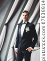 Happy handsome smiling groom posing with boutonniere 67939914