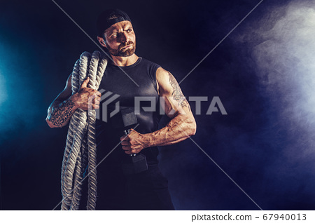 Bearded athletic looking bodybulder holding battle rope and barbbell on dark studio background with smoke. Strength and motivation 67940013